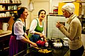 Women preparing Kaiserschmarrn, young woman tasting it, Austria