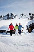 Three senior adult persons walking in snow, Fageralm, Salzburg, Austria