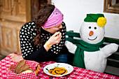 Woman sitting on a bench beside a snowman while eating pumpkin cream soup, Styria, Austria