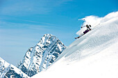 Skier downhill skiing in deep snow, Alagna Valsesia, Piedmont, Italy