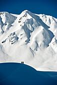 Two persons in snow-covered mountain scenery, Gargellen, Montafon, Vorarlberg, Austria