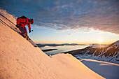 Skier downhill skiing in midnight sun, Lyngen Alps, Troms, Norway