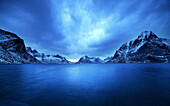Stormy sunset in a Norwegian fiord to the Lofoten Islands. In the background the snow-covered mountains.