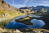 The calm surface of an alpine lake, under rocky ridges, in the early morning in summertime, Valsavarenche, Aosta Valley