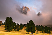 Pastures in autumn, with clouds, and behind them are raising the dolomite's profiles, in the sunset , Dolomites