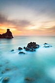 Sea's sunrise, with rocky banks and an ancient tower , Sicily
