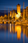 La Campanassa with buildings reflected in the sea with boats, Savona, Italy