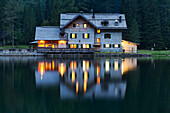 The refuge Nambino is reflected in the lake in the early evening light