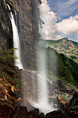 inside of the waterfall of Pis del Pesio with mountain view