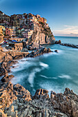 The warm lights of the sunset are painting Manarola, the second smallest village of the five that makes out Cinque Terre. The houses of the village lies on the edge of a cliff along Liguria. This is an UNESCO World Heritage Site, Cinque Terre National Par