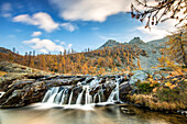 A little waterfall in the autumnal landscape of the Mont Avic natural park. Its water will flow to Lake Bianco, Mont Avic natural park, Aosta valley, Italy