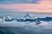 The unmistakable Matterhorn shape colored by the first lights of the sunrise from a peak in the Mont Avic Natural Parc, Aosta Valley, France