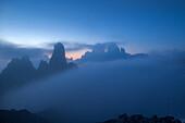The Caldini of Misurina and the Tre Cime di Lavaredo , Dreizinnen emerging out of a sea of fog at the twilight, Dolomites of Sesto, province of Belluno, Trentino Alto- Adige, Italy.