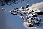 The typical pasture village of Lendine with its mountain huts covered with snow. Picture taken from the helicopter, Alps Spluga valley, Sondrio, Lombardy, Italy