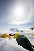 TALKEETNA, ALASKA - JUNE 17, 2008: A sun halo, which is an atmospheric phenomenon, forms over the tents of 14,200 foot basecamp.