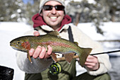 A fisherman smiles while holding up a beautiful rainbow trout caught on the Madison River, Montana.
