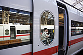 A couple kiss next to  an ICE train at the Leipzig train station in Germany.