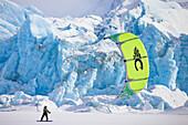Aaron Sales enjoys the views while kiting beneath a massive wall of ice on Inner Lake George, Alaska.