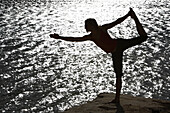 Sarah Chouinard holds a late afternoon yoga session standing bow pose, atop a boulder in the dry lakebed at Summersville Lake near Fayetteville, WV.
