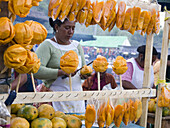 During a street festival, a woman cuts up mangoes to be eaten as street food snacks in San Bartolo, Sacatepequez, Guatemala.