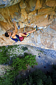 A rock climber in a blue tank top climbing a steep and technical route on yellow limestone at spring time in Rifle Colorado.