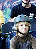 Blonde pre-teen boy in helmet poses, head and shoulders, sitting in front of older skateboarding teens at the Arts Barn skateboard park , on the town recreational campus in suburban Madison, Connecticut.