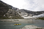 Paul Romer and guide Carlos Caballero kayaking on the Nigardsbreen Glacier,  near Jostedal, Norway. Part of the biggest ice cap in Europe.