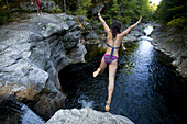 A group of teenagers jump off of a cliff at a secret swimming hole near Bethel, Maine.