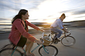 A young man and woman smile as they enjoy a sunny afternoon bike ride through an open street in Portland, ME. Motion Blur