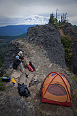 Two young women sit outside their tent while camping along Sleeping Beauty in the Pacific Northwest  Sleeping Beauty - a prominent rock precipice near the southern flanks of Mt Adams one of the Pacific Northwests great day hikes is a great playground for
