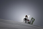 Portrait of backlit snowboarder standing with board on horizon.