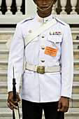 Front view of a male guard standing at his post, The Grand Palace, Bangkok, Thailand, on the 8 November 2009. The Grand Palace is a major architectural symbol of the The Royal Family. While a major tourist attraction to visitors, The Grand Palace is still