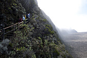 Hikers on the steep caldera wall on the Piton de la Fournaise, Reunion Island's active volcano. On August 1, 2010 the spectacular pitons, cirques and remparts of Reunion Island were inscribed in UNESCO's list of world heritage sites.