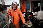 'Boat captain Kevin George stands on deck the vessel ''Casino'' while Native American divers, from the Suquamish Tribe, harvest geoducks in Puget Sound near Suquamish, Washington on Tuesday, January 18, 2011. Tribal divers can earn between $1000-2000 a da