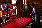 A woman works weaves spools of red silk threads onto a large loom in Myanmar.