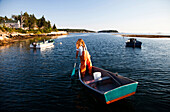 SEBASCO, MAINE, USA. A woman paddles her boat in a small harbor at sunset after she's been collecting lobster from underwater traps off the coast.