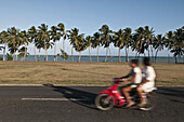 Two people riding a scooter, Aitutaki Island, Cook Islands, on the 6 August 2011. Motion blur,.