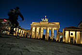 A man rides his bike towards The Brandenburg Gate, a former city gate and one of the most well-known landmarks of Berlin and Germany.