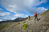 A group of  people wearing red jackets trekking in Tierra del Fuego,  Patagonia,  Chile.