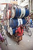 Dhaka,  Bangladesh - July 2011: Busy street  in Dhaka,  Bangladesh with a man pulling a wagon loaded high with 20 oil drums.
