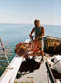 A worker aboard the boat Erin B. offloads a net of sea urchins onto the deck,  where they are inspected and counted.