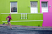 Katrin Schneider running trough the streets of the very colorful Bo-Kaap or Capa Malay Quarter of Cape Town. South Africa.