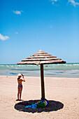 ROCKPORT, TEXAS, USA. A woman stands on an empty beach next to an umbrella.