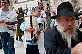 A boy carries the Torah at his Bar Mitzvah which is being celebrated in front of the Wailing Wall.