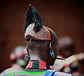Hamar men wear clay hair buns representing killing of an enemy or a dangerous animal. The hairdo lasts up to one year. Above the forehead, a small holder is made to hold ostrich feathers. To protect their hairdos, Hamar men at all times carry with them a