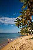 A woman enjoys a leisurely walk on a secluded beach in Las Terrenas.