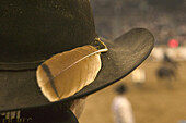 Detail shot of a feather on a cowboys hat.