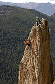 A guide on top of a rock spire gives advice to a climber during a precarious moment.  Topher Donahue / Aurora