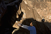 Johnny Landry spotting while Josh Haynes boulders Bloody Flapper rated V4, Hueco Tanks State Park, Texas.  Aaron Black / Aurora Photos