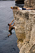 Brett Lowell shows off to the ladies above him while deep water soloing / rock climbing at Cala Sa Nau, Mallorca, Spain. Kim Miller, Catherine Brunel-Guitton and Melissa Lacasse watch from the cliff top above.